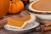 stock photo of pumpkin pie  - Slice of a pumpkin pie on wooden table. Pie and pumpkins on then background.