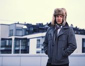 image of overcoats  - A man and wearing a fur hat and warm overcoat apartment buildings on background - JPG