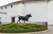stock photo of bullfighting  - Bull Statue In Front Of The Bullfighting Arena In Ronda Spain - JPG