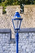 picture of lamp post  - Ornate blue lamp post stands before the rampart walls of The Tower of London - JPG