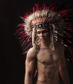 picture of headdress  - Naked indian strong man with traditional native american make up and headdress looking at the side - JPG