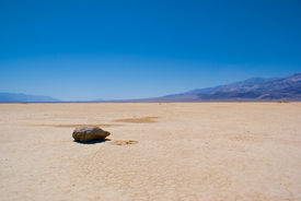 stock photo of mud pack  - Single grey rock sits on the hard dirt of a dry lake bed in southern California - JPG