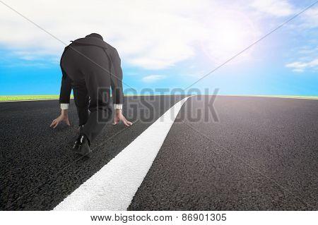 Businessman Ready To Run On Asphalt Road With Sky Sunlight
