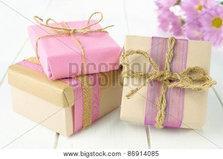Gift boxes with brown and pink wrapping on white wood