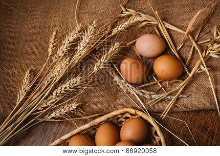 Fresh Brown Eggs And Wheat On Linen Background