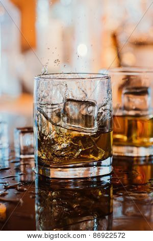 Whiskey Glass With Ice And Warm Light On Black Table With Reflection, Warm Atmosphere