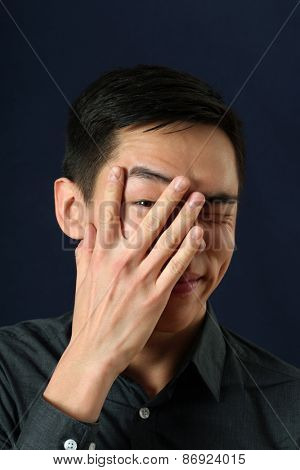 Young Asian man looking at camera through his fingers