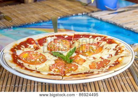freshly baked pizza with cheese and tomatoes served in small outdoor restaurant, meal time
