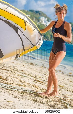 young woman kite surfer getting ready for kiting on sand tropical beach