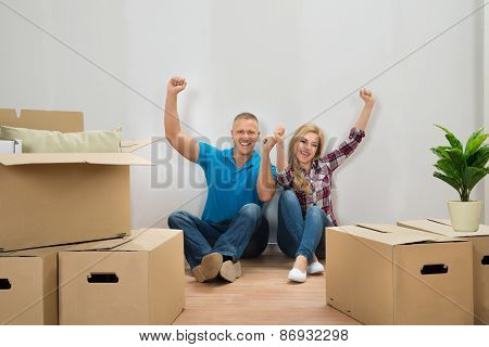 Young Couple Cheering In New Home
