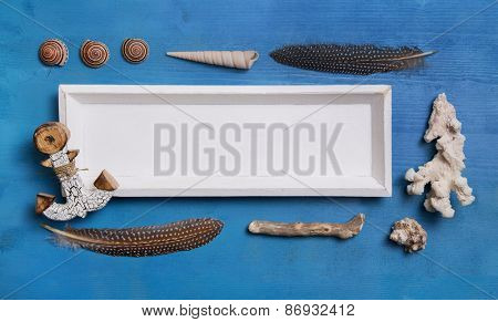 Blue and white nautical or maritime decoration with shells and a white wooden sign for an advertising board.