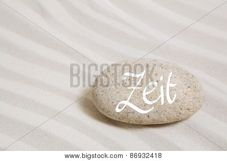 Stone in the sand with german text: time. Idea background for concepts.