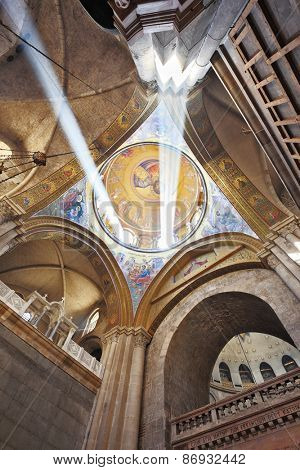 JERUSALEM, ISRAEL - MARCH 9, 2012: On the ceiling in the Hall of the Holy Sepulchre image of Christ the Savior. Gorgeous round arch ceiling lit by two bright rays of the sun