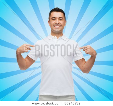 happiness, advertisement, fashion, gesture and people concept - smiling man in t-shirt pointing fingers on himself blue burst rays background