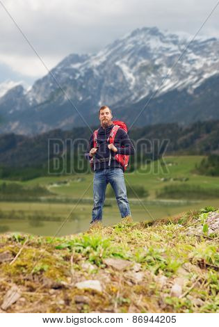travel, tourism, hike and people concept - tourist with beard and backpack standing on edge of hill over mountains background
