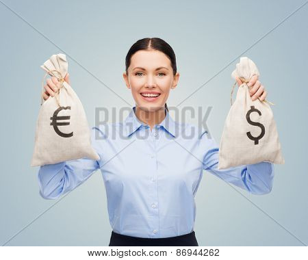 business, people, banking and finances concept - happy young businesswoman holding money bags with dollar and euro cash money over blue background