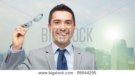 business, people, vision and happiness concept - happy smiling businessman in eyeglasses and suit over city background