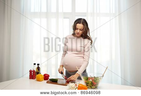 pregnancy, cooking food, healthy eating, people and expectation concept - pregnant woman with knife chopping tomato and preparing vegetable salad at home