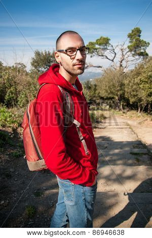 Young man backpacker tourist in park looking at camera