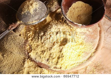 Whole flour with bowl and sieve on wooden cutting board, closeup