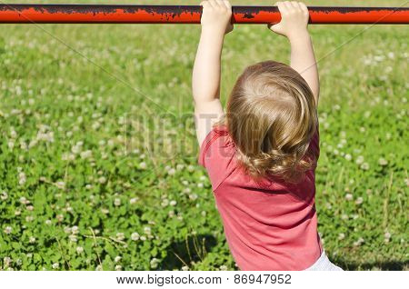 child playing in a park grabbing a railing