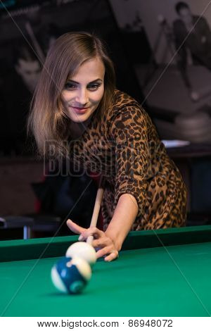 Pretty young girl is playing billiard or pool at a date in a bar