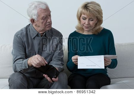 Aged Couple Analyzing Unpaid Bills