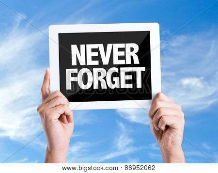Tablet pc with text Never Forget with sky background