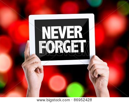 Tablet pc with text Never Forget with bokeh background