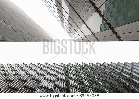 A photo looking up capturing three different buildings on an angle