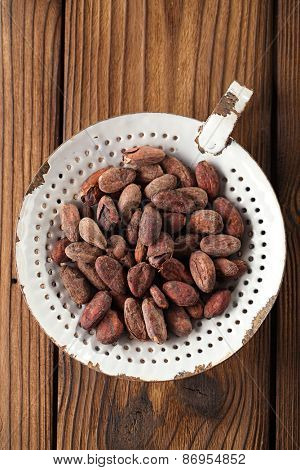 roasted cocoa chocolate beans in old enamel sieve, textured  wooden background