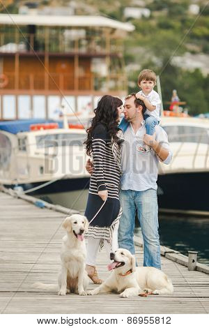 Happy family spends time on the pier next to the yacht club.