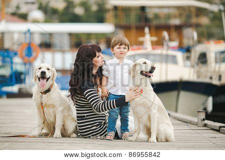 Mother and young son and their dog sit on the pier near the yacht club.