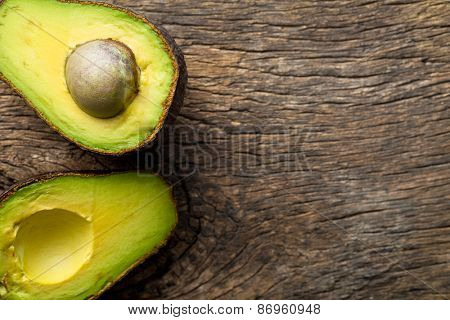 halved avocado on old wooden table