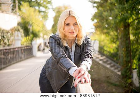 Pretty Girl Standing On The Bridge Leaning On Railing