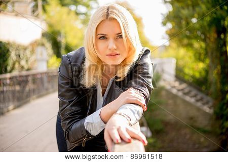 Beautiful Girl Leans On The Railing Of The Bridge