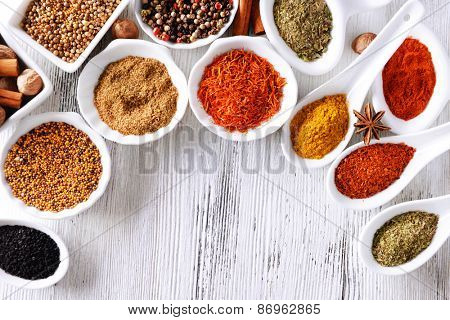 Different kinds of spices in ceramics bowls and spoons on wooden background