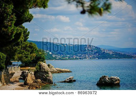 city and sea view with stones on beach at Miramare castle, Trieste, Italy