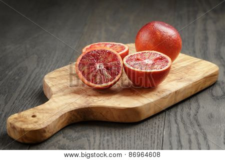 red sicilian oranges sliced on olive board