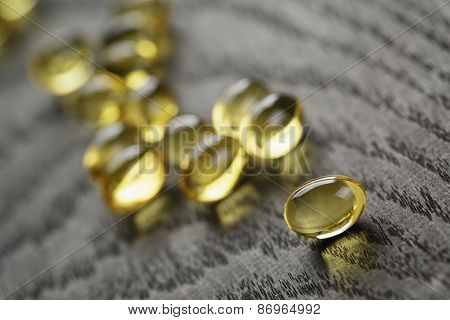 heap of fish oil omega capsules on wooden table