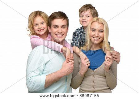 Cheerful smiling family of four looking at camera