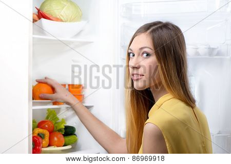 Young beautiful woman picking food from fridge