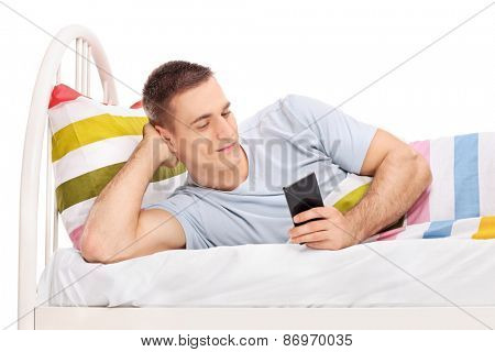 Studio shot of a relaxed young man lying in a bed and surfing the internet on his cell phone isolated on white background