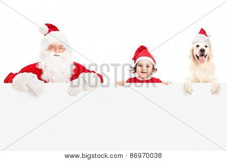 Santa Claus, a cute baby girl and a Labrador retriever dog posing behind a blank signboard isolated on white background