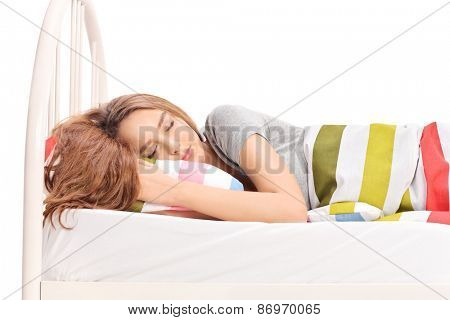 Studio shot of a beautiful young girl sleeping on a comfortable bed covered with a blanket isolated on white background