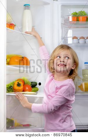 Funny smiling girl trying to pick food from fridge