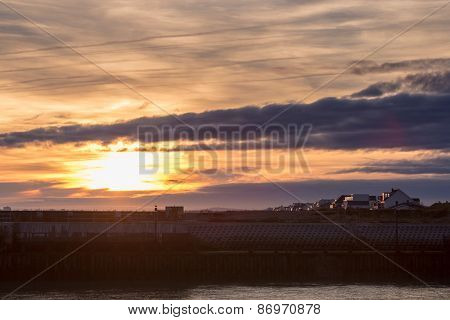 Sunset over a beach and harbour wall