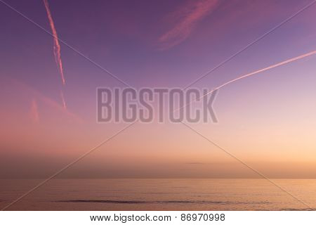 Sunset, vapour trails and sea