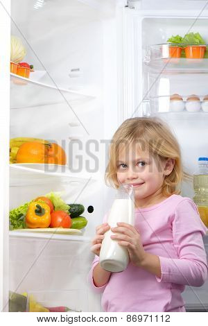 Little cute girl holding bottle of milk near open fridge