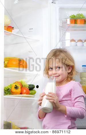 Little cute girl holding bottle of milk near open fridge